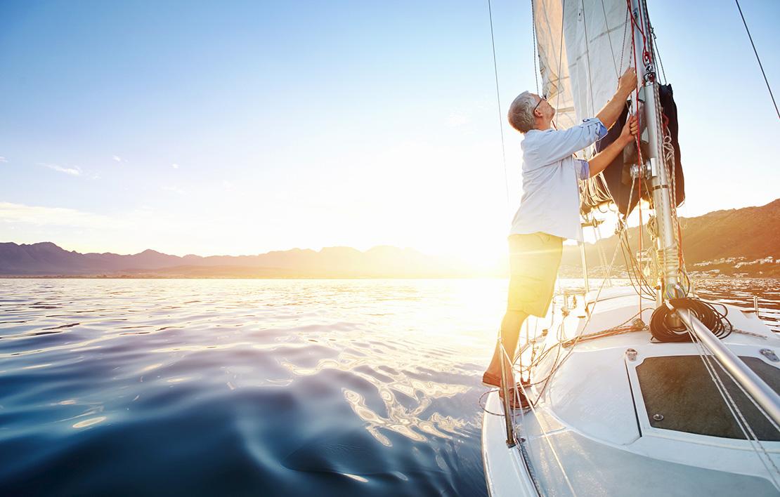 Man on sailboat raising sail
