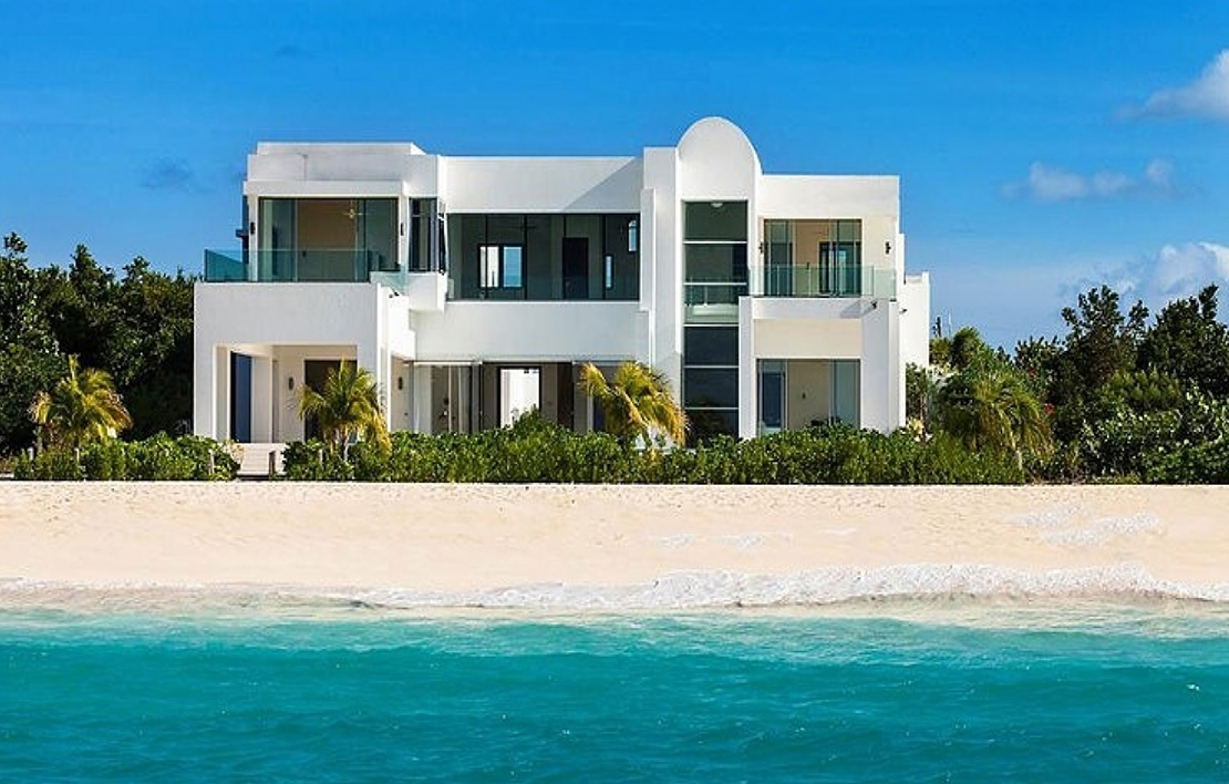 A sizable house with full glass windows and doors located very close to the water