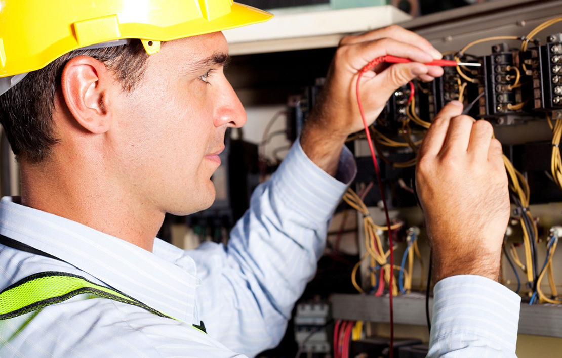 Male electrician wiring a panel